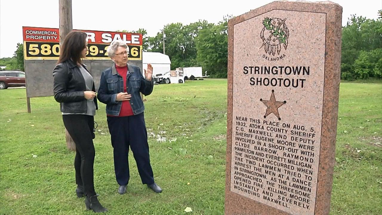 Atoka Museum director Gwen Walker next to a memorial honoring two Atoka County lawmen involved in a 1932 shootout with outlaw Clyde Barrow. (KTEN)