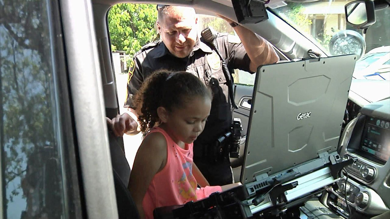 A Denison police officer lets a Houston Elementary student sit in his patrol car. (KTEN)