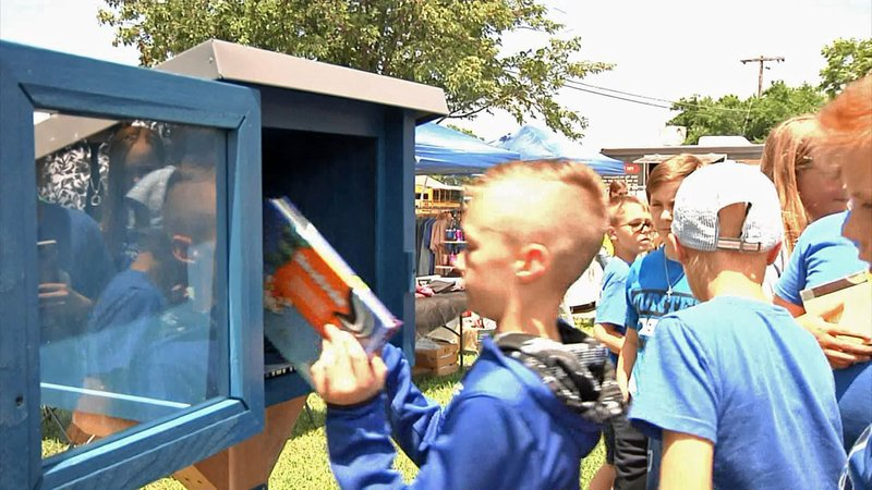 Gunter 5th graders load books into the new Little Free Library. (KTEN)