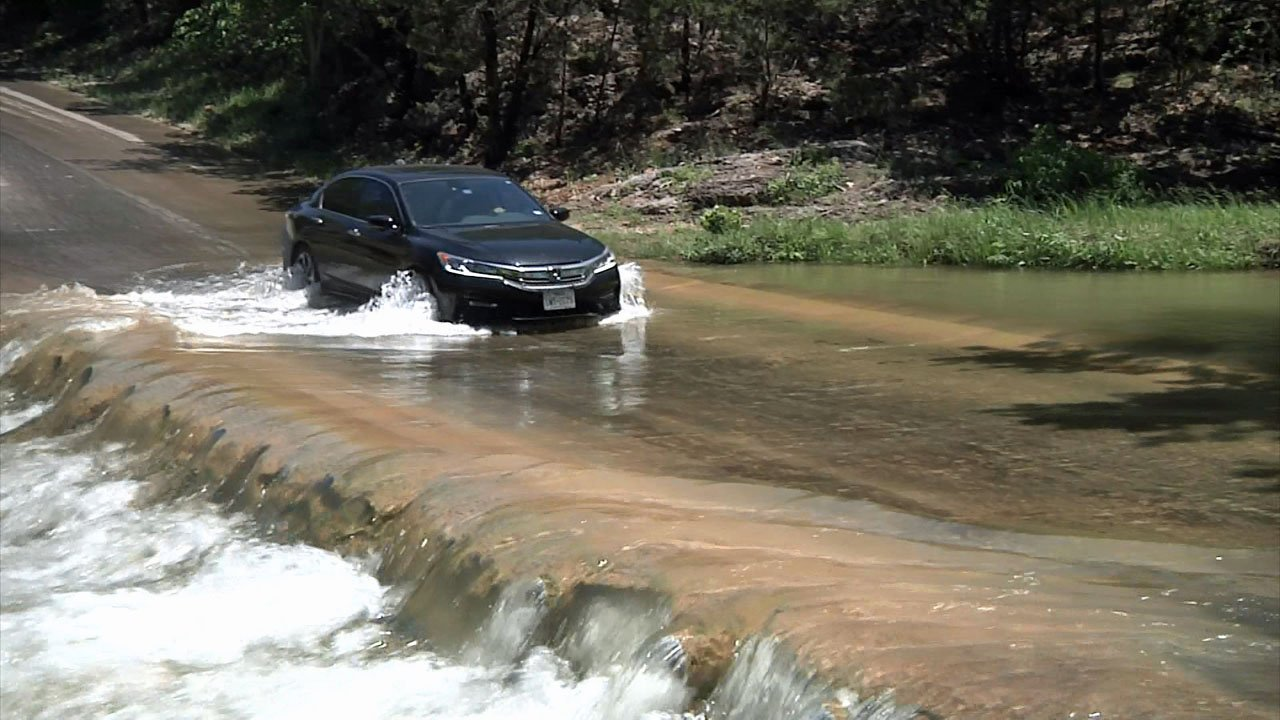 A car plows through a low water crossing at Turner Falls Park. (KTEN)