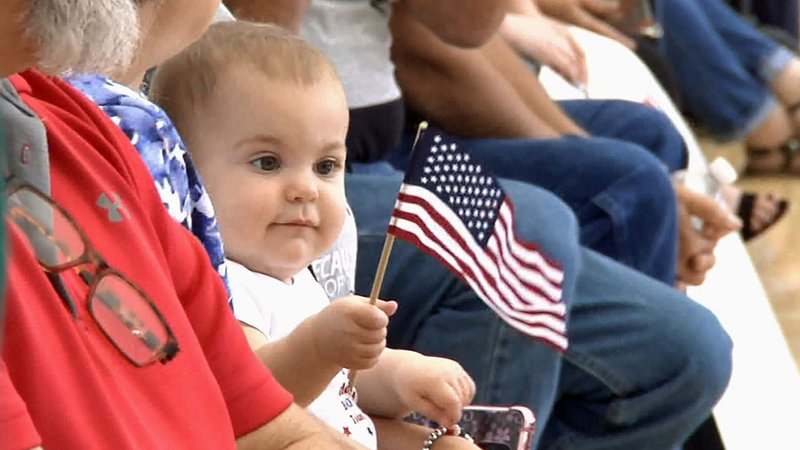 An infant holds a flag as an Oklahoma Army National Guard unit returns to Ada from Kuwait. (KTEN)
