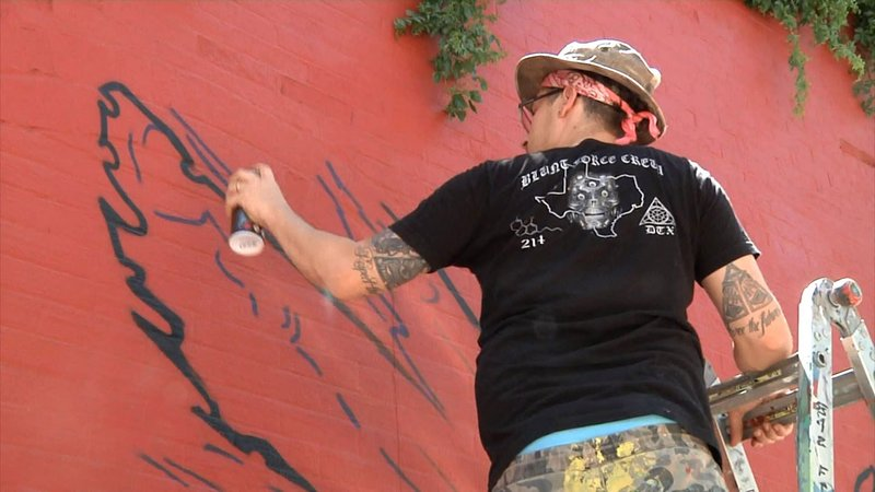 "Jerod ""DTOX"" Davies paints a mural in downtown Denison. (KTEN)"