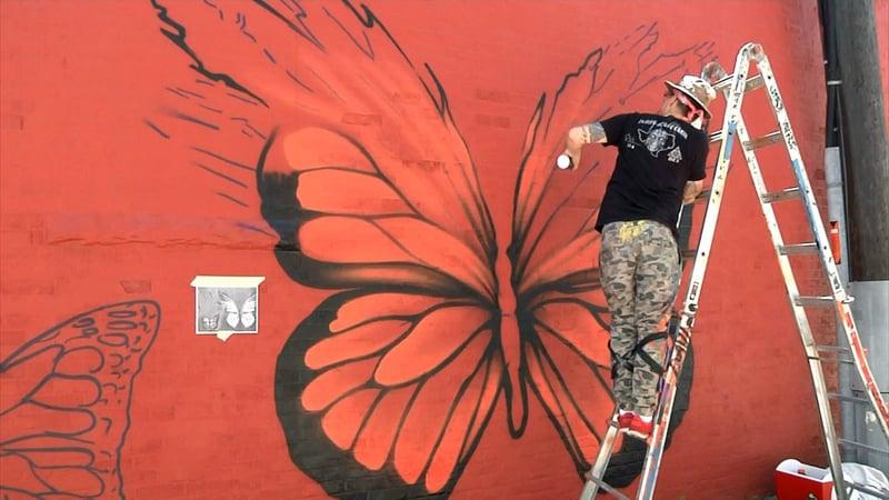 "Jerod ""DTOX"" Davies paints a butterfly-themed mural in downtown Denison on June 2, 2019. (KTEN)"