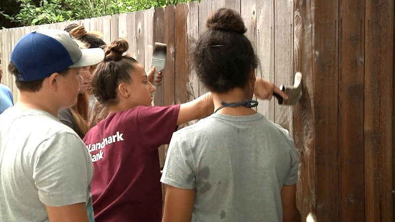 SAY campers paint a fence. (KTEN)