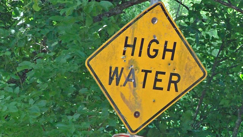 A sign warns motorists about the Greenwood low water crossing on Coatsworth Road. (KTEN)