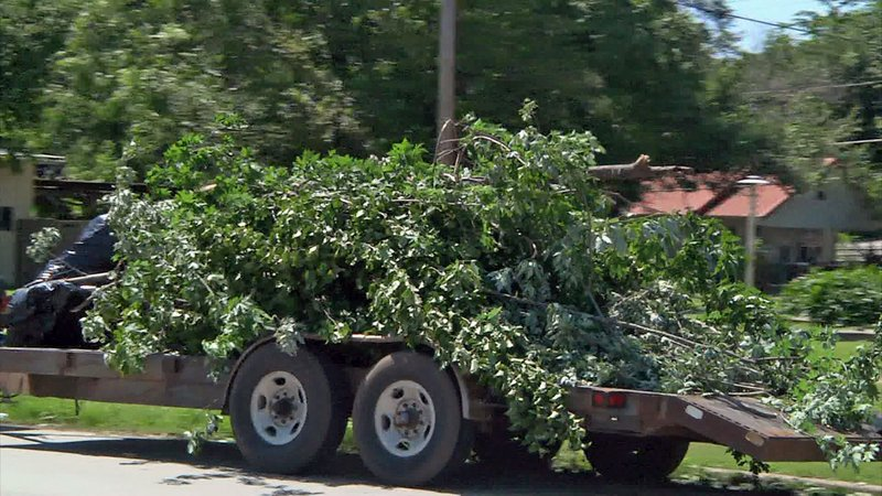 A load of storm debris in Ada is hauled away on a trailer. (KTEN)