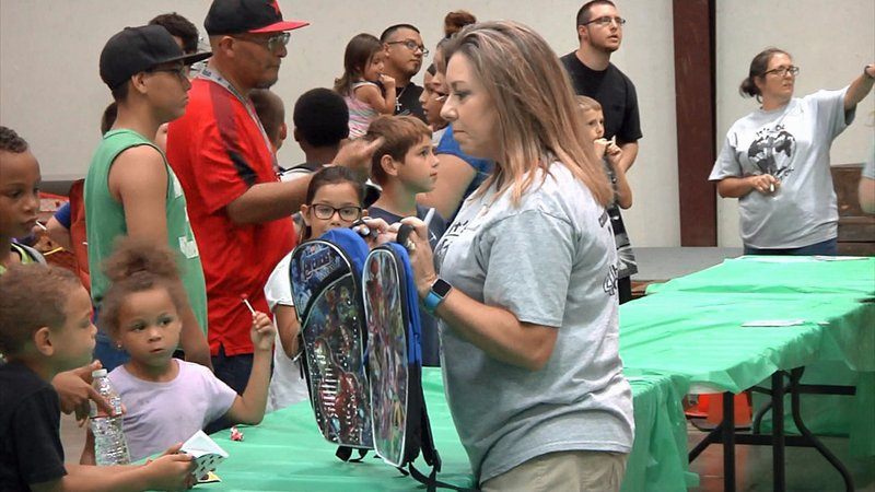 A 4 His Glory Ministries volunteer offers free backpacks to Sherman students. (KTEN)