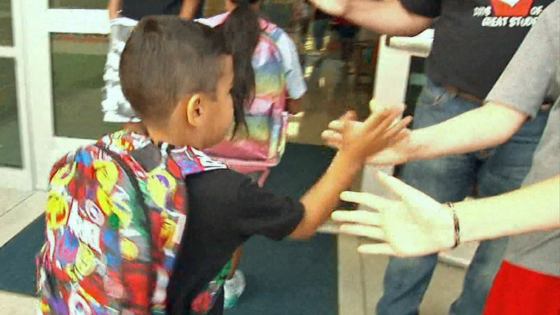 High fives all around as Sory Elementary DOGS greet arriving students. (KTEN)
