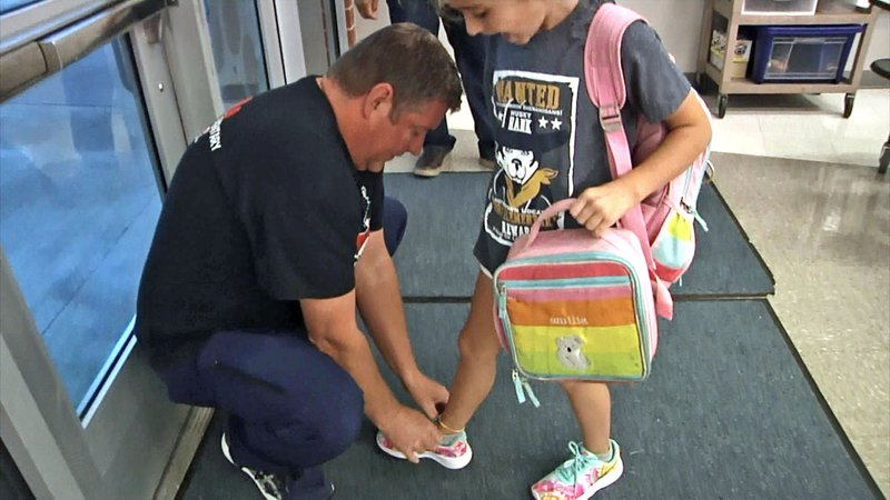 One of the Dads of Great Students ties the shoe of a Sory Elementary student. (KTEN)
