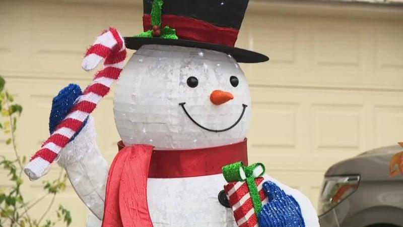 Nick and Claudia Simonis say they won't take down their Christmas decorations as demanded by their HOA in San Antonio. (WOAI via NBC News)