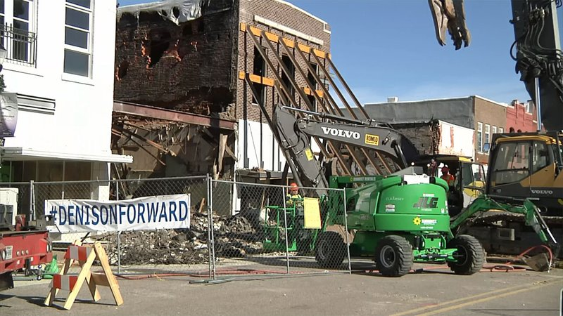 Workers razed the ruins of a fire-damaged building in downtown Denison. (KTEN)