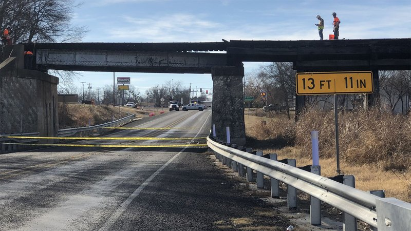 Workers examine damage to a railroad bridge over US 69 in Bells on December 4, 2019. (KTEN)