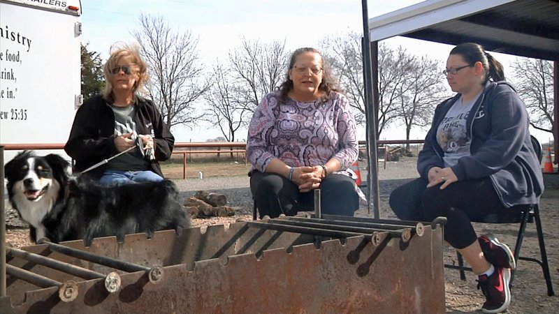 Volunteers at King's Trail Cowboy Church wait for Project Christmas donations at a fire outside the church. (KTEN)