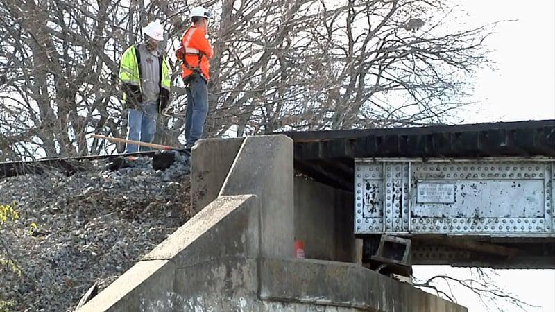 Workers examine damage to the railroad bridge over US 69 in Bells, Texas. (KTEN)