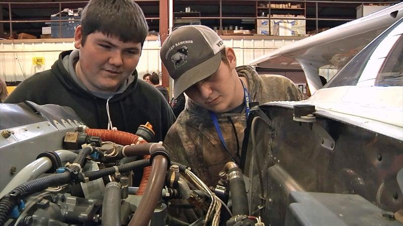 High school students check an engine at SOSU's Aviation Day. (KTEN)